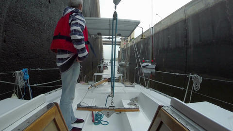 Senior captain on deck, sailboat ready to pass through lock Footage