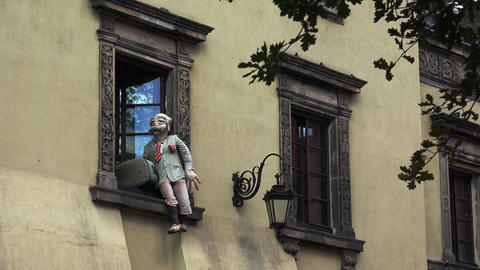 Doll tourist traveler in the window of an old house in Warsaw. Poland. 4K Footage