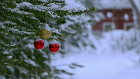 Snowfall and Christmas Balls on the Tree Near the House. Seamless Loop Footage