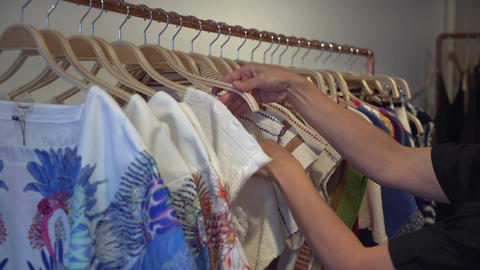 Woman looking through garments in a clothing store Footage
