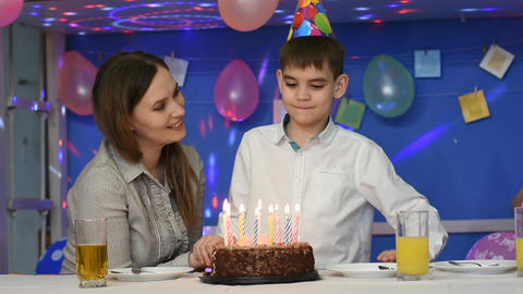 Boy blows out candles on a birthday cake Live Action