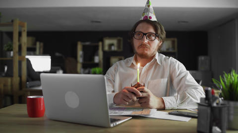Sad businessman celebrating a lonely birthday in the office Live Action