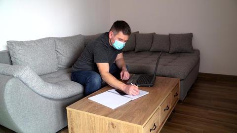 Quarantine coronavirus COVID19 distance job. Young businessman in mask talking Live Action