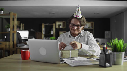 Alone businessman is opening gift on birthday in the office Live Action