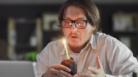 Manager celebrating a lonely birthday and blows out a candle in the office Live Action