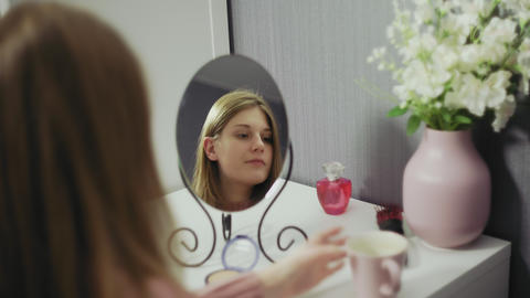 Beauty woman applying makeup and drinking tea. Beautiful girl looking in the Live Action