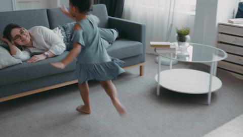 Little young girl playful happy run to mother babysitter nanny lying sofa in Live Action