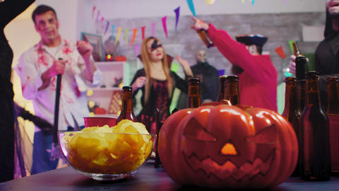 Scary pumpkin on the party while group of people are dancing celebrating Live Action