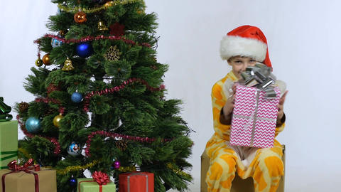 Cheerful joyful girl sitting on a box with a gift near the New Year tree Live Action