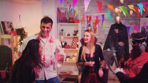 Group of happy people having fun and dancing at halloween party Live Action