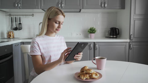 Attractive woman using tablet device while having breakfast on her kitchen Live Action