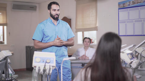 Confident bearded Middle Eastern lecturer teaching dentistry to Caucasian women Live Action