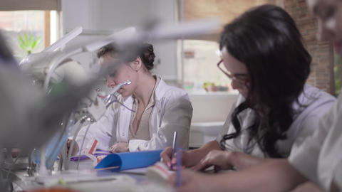 Close-up of female Caucasian dentistry students in white uniform writing test on Live Action