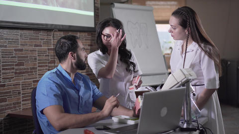 Modern Middle Eastern teacher explaining dentistry to students using laptop Live Action