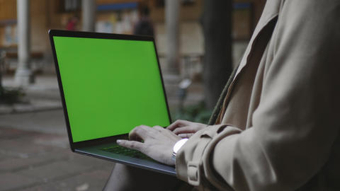 Student typing laptop with green screen. Woman hands working computer outdoors Live Action