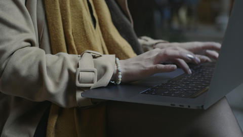 Student using touchpad on laptop outdoors. Woman hands typing laptop outside Live Action
