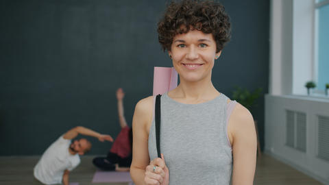 Portrait of attractive girl in sports outfit holding yoga mat smiling in studio Live Action