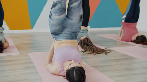 Attractive slender women doing yoga in studio laying on mats with legs up Live Action