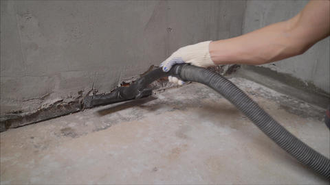 A worker using a vacuum cleaner removes construction debris. A worker is Live Action