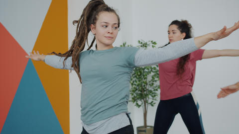 Pretty young lady in sports clothing exercising indoors in yoga club focused on Live Action