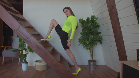 Woman in high heels doing lunge exercise on stairs Live Action