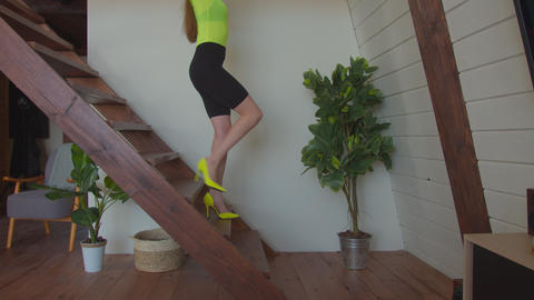 Lovely female in high heels descending stairs indoors Live Action