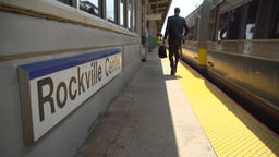 Business commuter at Rockville Centre train passing the station sign Footage
