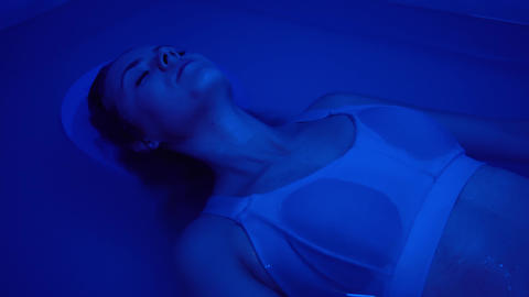 A young woman in a swimsuit is immersed in a hot tub or pool with sea salt Live Action