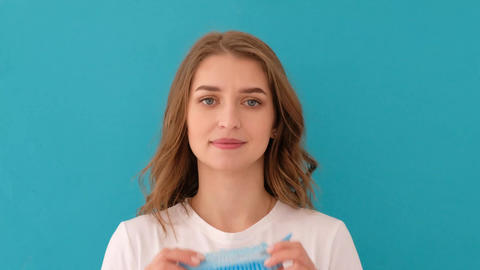 Calm young woman putting on blue medical hat Live Action