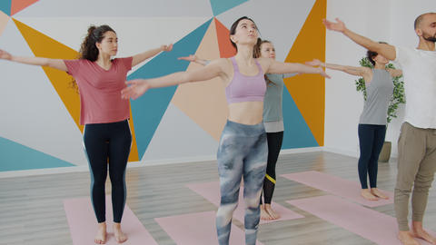 Women and man in sportswear doing yoga balancing asanas in sports club Live Action
