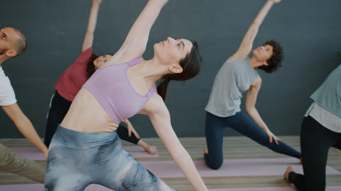 Girls and guy practising yoga stretching body then relaxing in meditative Live Action