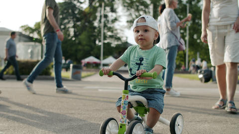 Focused toddler in amusement park. Little kid making first try on bike outside Live Action
