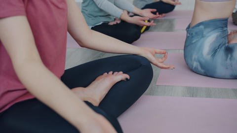 Slow motion of pretty young women meditating in yoga class in lotus position Live Action