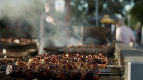 Shish kebabs preparing on skewers outdoors. Chef male cooking meat outside Live Action