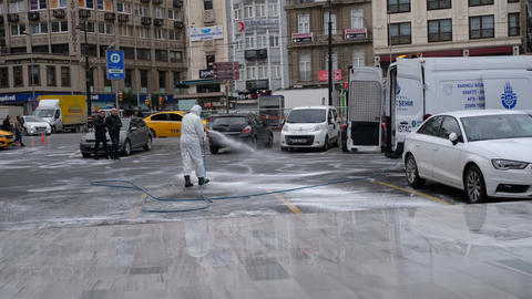 A man in protective equipment and wearing a mask, cleaning disinfecting the streets in istanbul Live Action