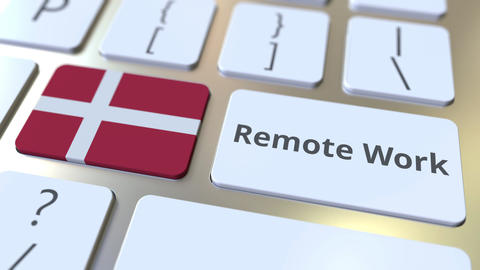 Remote Work text and flag of Denmark on the computer keyboard. Telecommuting or Live Action