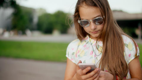 Smiling girl playing games on mobile phone outdoors. Girl standing in park Live Action