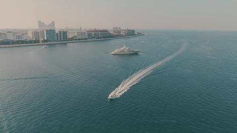 Aerial view of cruising motorboat and unknown anchored luxury motor yacht Live Action