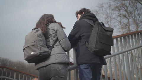 Back view of positive Caucasian boy and girl chatting and hugging in city park Live Action
