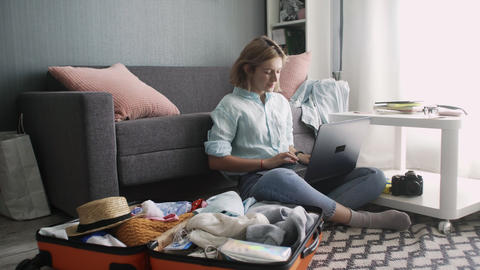 Cute girl typing on a laptop and getting ready for road trip Live Action