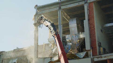 excavator ruins column of dangerous hockey arena building Live Action