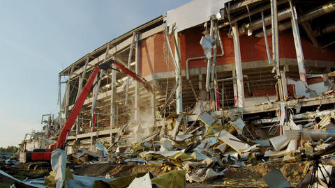 excavator destroyer works on destroying hockey arena in dust Live Action