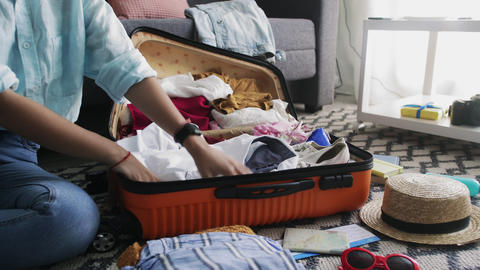 Travel woman packing suitcase, getting ready for road trip, preparing luggage Live Action