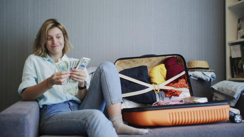 Happy woman counts money and thinks about her future vacation Live Action