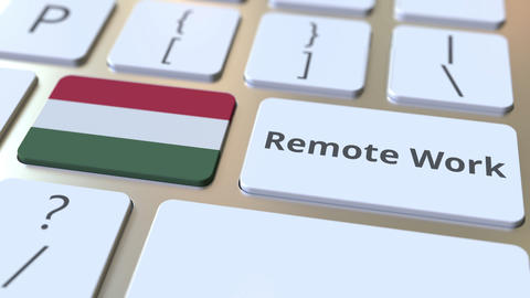 Remote Work text and flag of Hungary on the computer keyboard. Telecommuting or Live Action