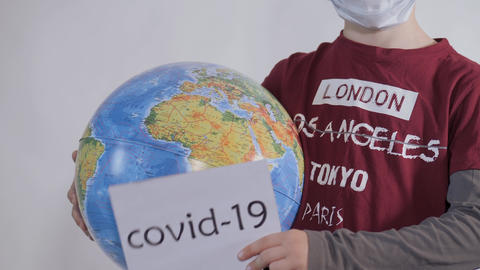 Boy holds a globe, a model of the planet Earth. Child is holding a sign with the Live Action