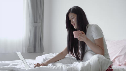 zoom in video shot of beautiful Asian woman sitting on a bed is using a laptop to communicate the Live Action