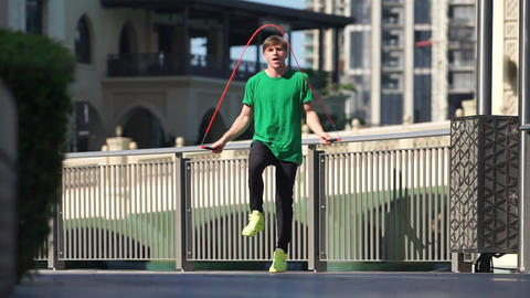 Man jumping with jump rope on the cityscape background of Dubai. Slow motion Live Action