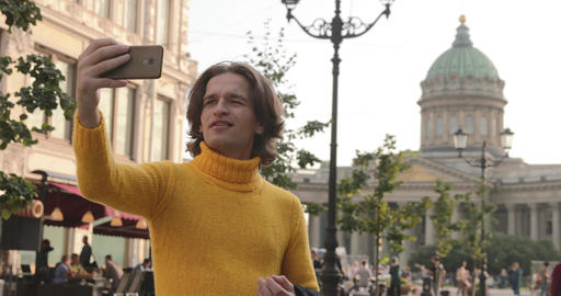 The handsome men does selfie, Look from outside, he dressed in a yellow sweater Live Action