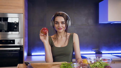 Appealing satisfied joyful young woman in headphones looking at camera while Live Action